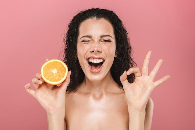 Schönheitsbild der jungen frau mit dem langen haar, das lächelt und stück orange hält, lokalisiert über rosa hintergrund