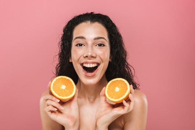 Schönheitsbild der kaukasischen halbnackten frau mit dem langen haar, das lächelnd und die stücke der orange hält, lokalisiert über rosa hintergrund