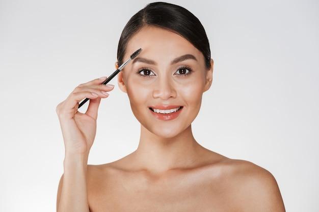 Schönheitsbild der recht jungen frau mit dem haar im brötchen, das auf kamera schaut und ihre augenbrauen mit dem pinsel, lokalisiert über weiß kämmt
