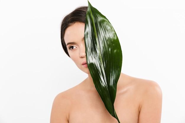 Schönheitsbild der weiblichen asiatischen frau mit frischer sauberer haut, die ihr gesicht mit grünem blatt bedeckt, lokalisiert über weiß