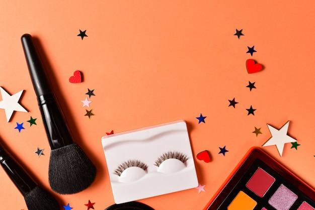 Schönheitsbloggertext auf einem orange hintergrund. professionelle trendige make-up-produkte mit kosmetischen schönheitsprodukten, lidschatten, wimpern, pinseln und werkzeugen.