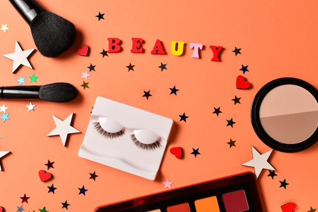 Schönheitsbloggertext auf einer orange oberfläche. professionelle trendige make-up-produkte mit kosmetischen schönheitsprodukten, lidschatten, wimpern, pinseln und werkzeugen.