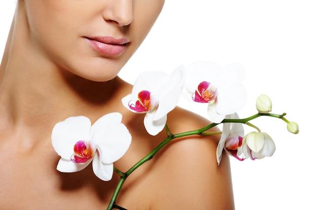 Schönheitsblume, die auf nackter weiblicher schulter mit sauberer gesunder haut liegt