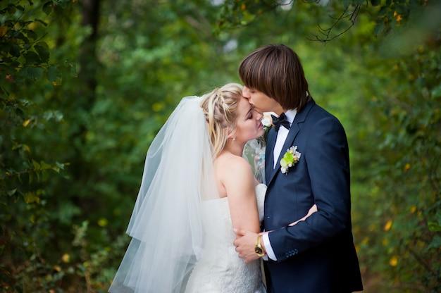 Schönheitsbraut und -bräutigam auf hochzeit gehen in sommerpark