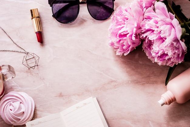 Schönheitsebene lag mit einem tagebuch, einem smartphone, zubehör und pfingstrosen auf einem marmorhintergrund