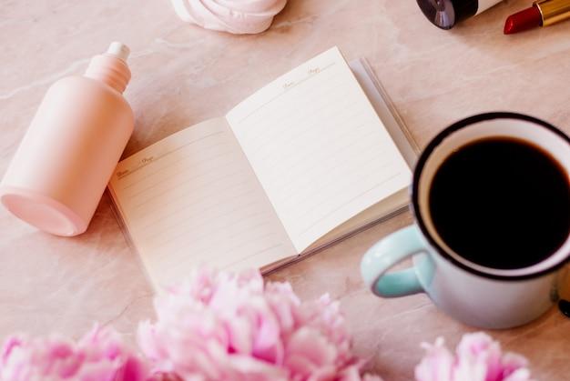 Schönheitsebene lag mit einem tagebuch, einem tasse kaffee, zubehör und pfingstrosen auf einem marmorhintergrund