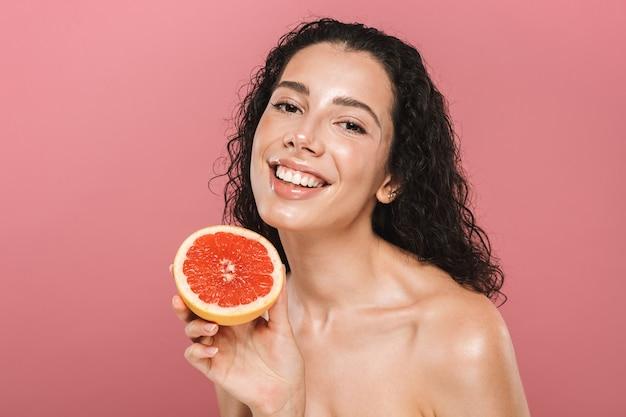 Schönheitsfoto der entzückenden jungen frau mit den langen haaren, die lächeln und stück grapefruit halten, lokalisiert über rosa hintergrund