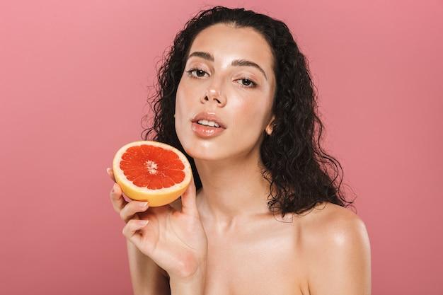 Schönheitsfoto der frau mit dem sauberen gesicht und den langen haaren, die lächeln und stück grapefruit halten, lokalisiert über rosa hintergrund