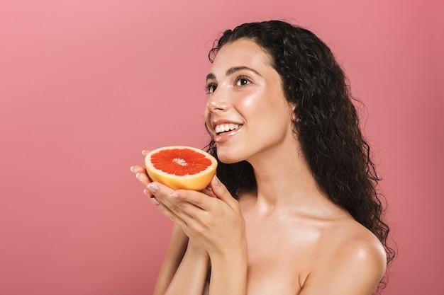 Schönheitsfoto der kaukasischen frau mit den langen haaren, die lächeln und stück grapefruit halten, lokalisiert über rosa hintergrund