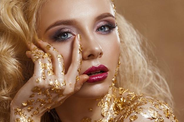 Schönheitsfrau, blondes haar, professionelles make-up, goldene farbe.