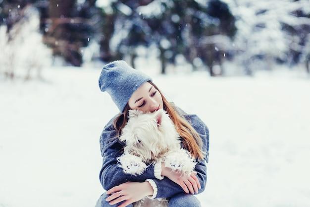 Schönheitsfrau, die draußen ihren hund umarmt