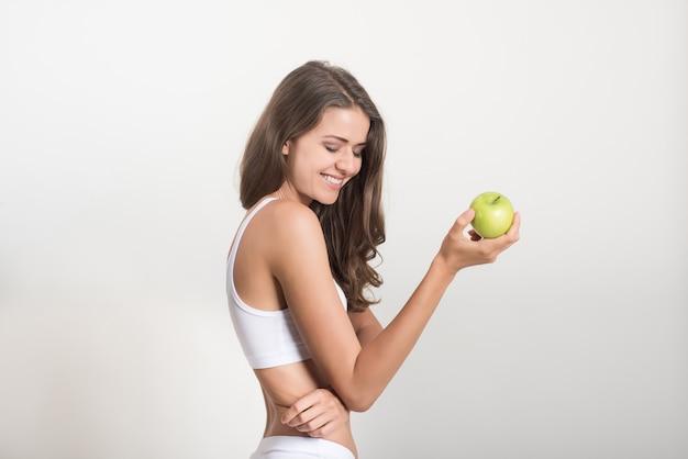 Schönheitsfrau, die grünen apfel hält, während sie auf weiß lokalisiert werden