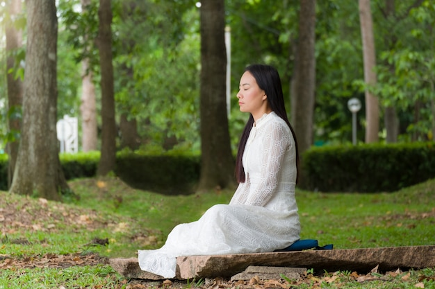 Schönheitsfrau, die im garten meditiert.
