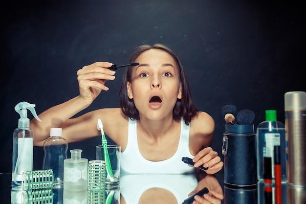 Schönheitsfrau, die make-up anwendet. schönes mädchen, das im spiegel schaut und kosmetik mit einem großen pinsel anwendet