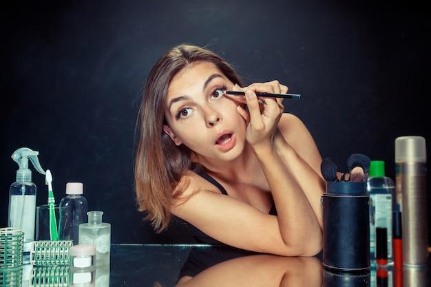Schönheitsfrau, die make-up anwendet. schönes mädchen, das im spiegel schaut und kosmetik mit einem pinsel anwendet
