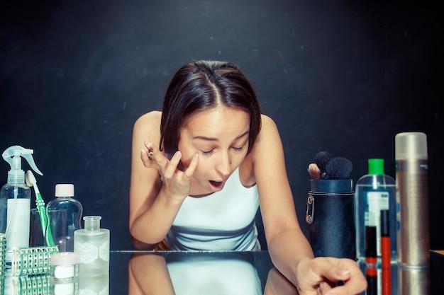 Schönheitsfrau, die make-up anwendet. schönes mädchen, das in den spiegel schaut und kosmetik mit einem eyeliner anwendet. kaukasisches modell im studio