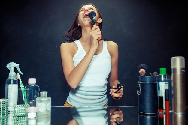 Schönheitsfrau, die make-up anwendet. schönes mädchen, das in den spiegel schaut und kosmetik mit einem großen pinsel anwendet. kaukasisches modell im studio singendes lied