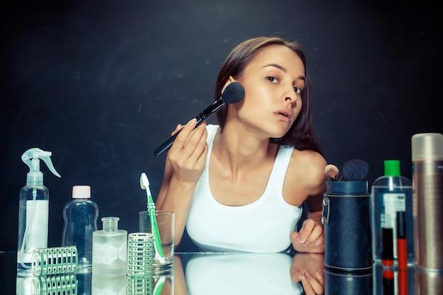 Schönheitsfrau, die make-up anwendet. schönes mädchen, das in den spiegel schaut und kosmetik mit einem großen pinsel anwendet. kaukasisches modell im studio