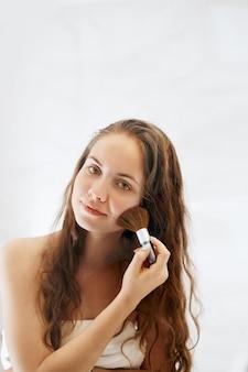 Schönheitsfrau, die make-up anwendet. schönes mädchen, das in den spiegel schaut und kosmetik mit einem großen pinsel anwendet. mädchen wird rot auf den wangenknochen. pulver, rouge
