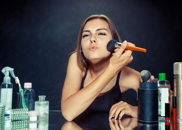 Schönheitsfrau, die make-up anwendet. schönes mädchen, das in den spiegel schaut und kosmetik mit einem großen pinsel anwendet. morgen, make-up und menschliches gefühlskonzept. kaukasisches modell im studio