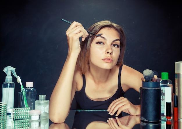 Schönheitsfrau, die make-up anwendet. schönes mädchen, das in den spiegel schaut und kosmetik mit einem großen pinsel anwendet. morgen, make-up und menschliches gefühlskonzept