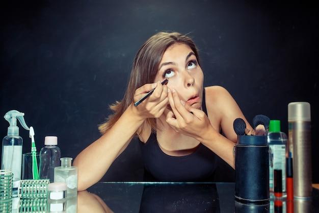 Schönheitsfrau, die make-up anwendet. schönes mädchen, das in den spiegel schaut und kosmetik mit einem pinsel anwendet. morgen, make-up und menschliches gefühlskonzept. kaukasisches modell im studio