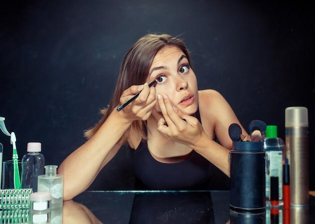 Schönheitsfrau, die make-up anwendet. schönes mädchen, das in den spiegel schaut und kosmetik mit einem pinsel anwendet.
