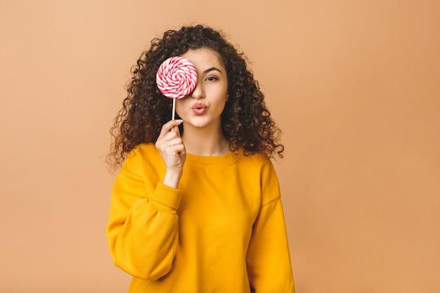 Schönheitsfrau, die rosa süße bunte lutscherbonbons hält, lokalisiert auf beigem hintergrund.