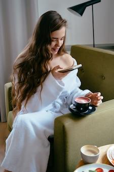 Schönheitsfrau, die zu hause smartphone auf dem sofa verwendet
