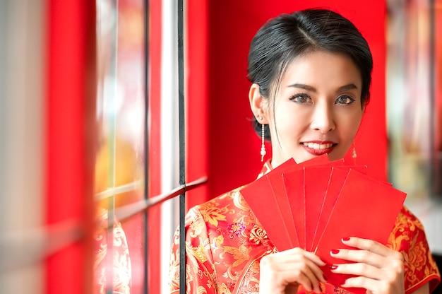 Schönheitsfrau im roten kleid traditionellem cheongsam, das rote umschläge hält