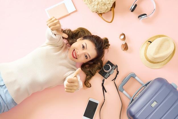 Schönheitsfrau lächelt glücklich und zeigt ihnen auf rosafarbenem boden den daumen. liegen mit ihrem reisegepäck