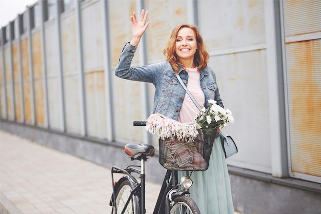 Schönheitsfrau mit fahrrad winkt für jemanden
