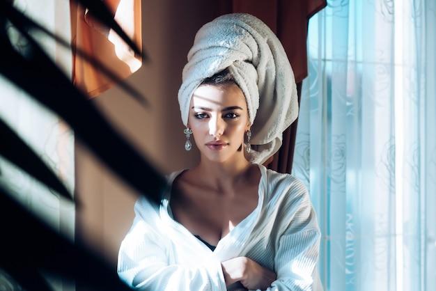 Schönheitsfrau mit handtuch auf kopf entspannend nach spa oder morgendusche frau im bademantel nach wellness- und hautpflegeprozeduren ruhen wellness- und pflegekonzept