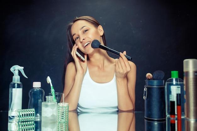 Schönheitsfrau mit handy, das make-up anwendet. schönes mädchen, das in den spiegel schaut und kosmetik mit einem großen pinsel anwendet. kaukasisches modell im studio