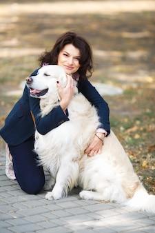 Schönheitsfrau mit ihrem hund, der draußen spielt. frau, die labrador retriever im park geht.