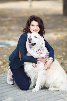 Schönheitsfrau mit ihrem hund, der draußen spielt.