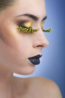 Schönheitsfrau mit langen gelben wimpern und schwarzen lippen auf blauem hintergrund
