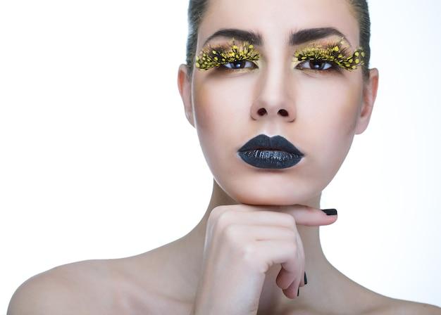 Schönheitsfrau mit langen gelben wimpern und schwarzen lippen auf weißem hintergrund