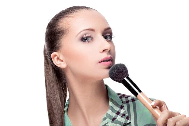 Schönheitsfrau mit make-up-pinseln. natürliches make-u