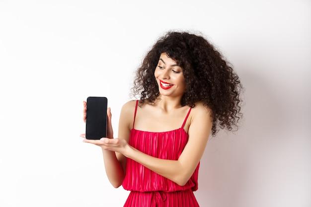 Schönheitsfrau mit make-up und lockigem haar, zeigt leeren smartphone-bildschirm, demonstrieren app, stehend auf weißem hintergrund.