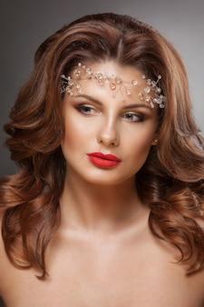 Schönheitsfrau mit schönem make-up. glamour girl. braunes haar, welliges haar, klare haut, schönes gesicht.