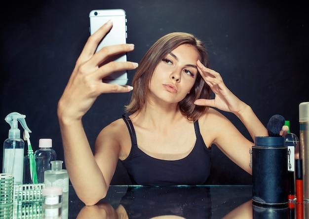 Schönheitsfrau nach dem auftragen von make-up. schöne frau mit make-up. schönes mädchen, das das handy betrachtet und selfie-foto macht. kaukasisches modell im studio