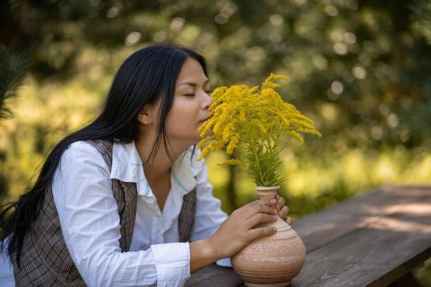 Schönheitsfrau schnüffelt aroma von gelben blumen am warmen tag im garten. asiatische brünette, die am hölzernen tisch mit blumenstrauß von solidago darauf ruht. weibliches porträt in der natur im freien.
