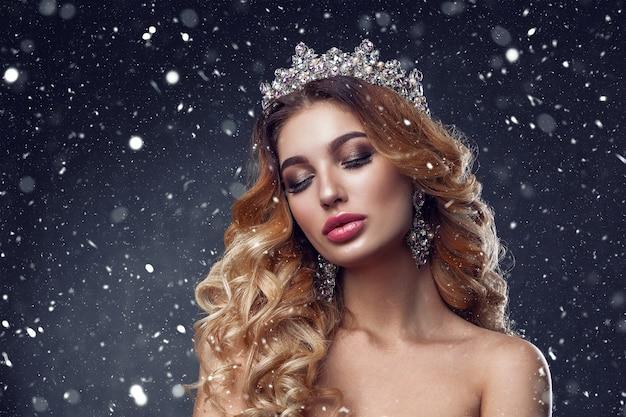 Schönheitsfrauengesicht mit schönen make-upfarben. das bild der königin. dunkles haar, eine krone auf dem kopf, klare haut, schönes gesicht, pralle lippen.