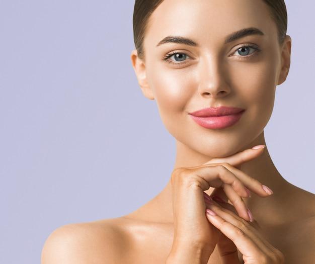 Schönheitsfrauenhautpflege schöne weibliche hand, die gesicht kosmetisches mädchenmodell über blauem hintergrund berührt