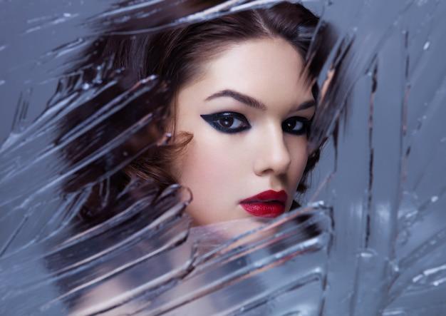 Schönheitsfrauenmodell mit make-up und dem gelockten haar durch den spiegel kreativ in den kalten tönen auf grauem hintergrund
