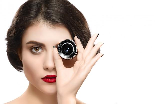 Schönheitsfrauenporträt, das kameraobjektiv auf auge hält