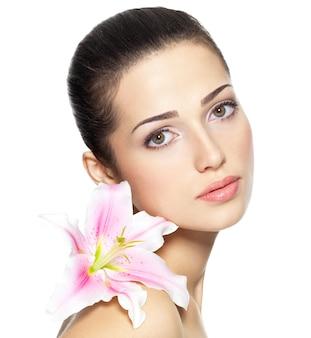 Schönheitsgesicht der jungen frau mit blume. schönheitsbehandlungskonzept. porträt über weißer wand