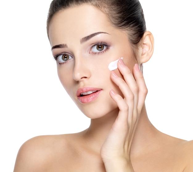 Schönheitsgesicht der jungen frau mit kosmetischer creme auf einer wange. hautpflegekonzept. nahaufnahmeporträt lokalisiert auf weiß.