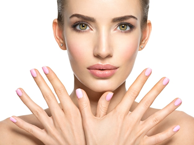 Schönheitsgesicht der jungen schönen frau - lokalisiert auf weiß. frau mit schönem fingernagel. hübsches junges mädchen zeigt hände vor gesicht mit rosa nägeln